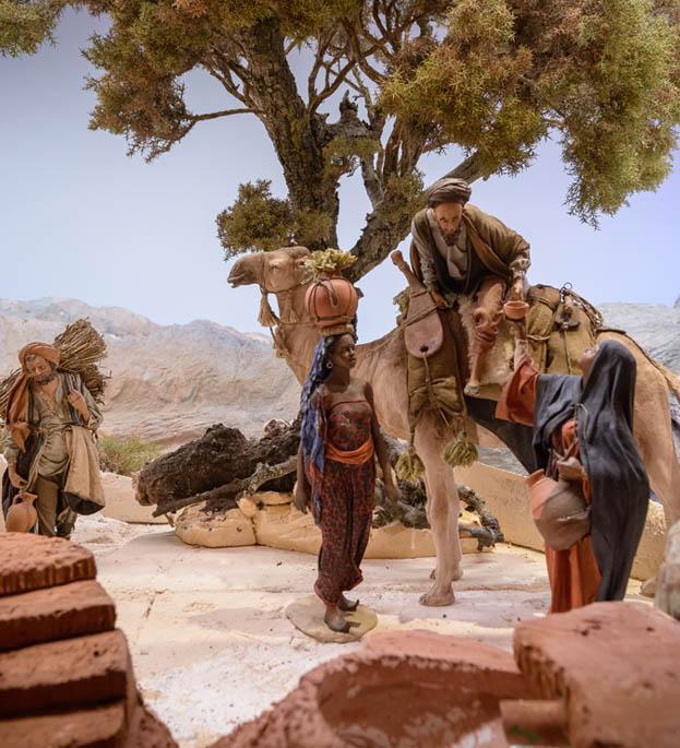 Mujer dando agua a hombre en camello